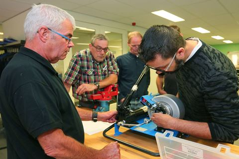 Meerdere personen zijn bezig voor de cursus Hydrauliek slangassemblage