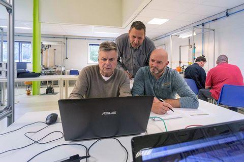 3 personen zijn bezig voor cursus Meet en regeltechniek basis