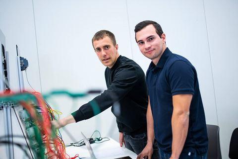 Twee cursisten PLC systemen kijken in camera